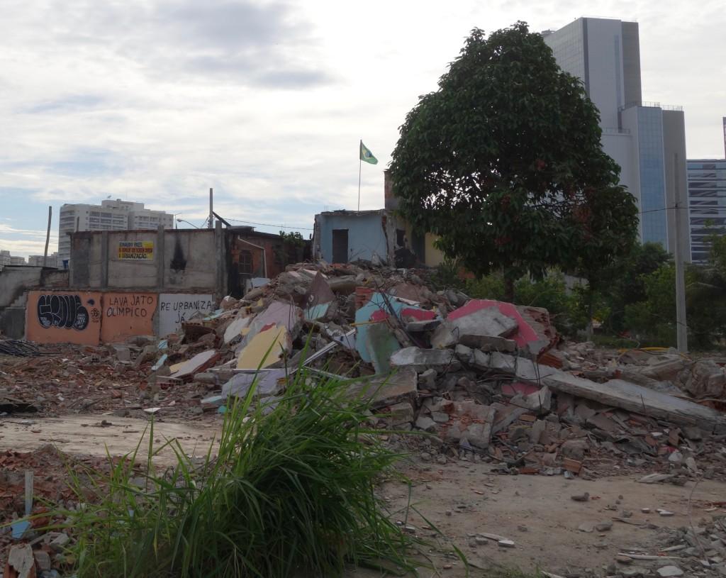 """Os moradores que restam na Vila Autódromo vivem entre os escombros de casas demolidas enquanto o Parque Olímpico cresce ao fundo. Os grafites exigem a urbanização da Vila Autódromo e fazem referência ao envolvimento dos projetos de construção das obras das Olimpíadas no """"Lava Jato"""", escândalo de corrupção que está sendo investigado."""