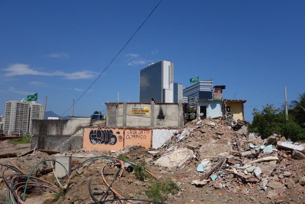 """Os moradores remanescentes da Vila Autódromo vivem entre ruínas, enquanto o Parque Olímpico é erguido ao fundo. O grafite denuncia que empreiteiras por trás dos projetos olímpicos estão envolvidas no escândalo de corrupção da """"Operação Lava Jato""""."""