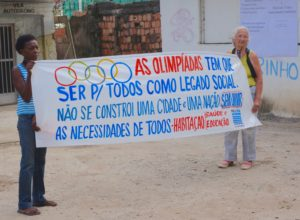 "Residents in Vila Autódromo, a neighbourhood decimated by forced evictions prior to the 2016 Olympics, protest: ""The Olympics should be for everyone as a social legacy. One cannot construct a city and a nation without listening to everyone's needs. Housing, health and education""."